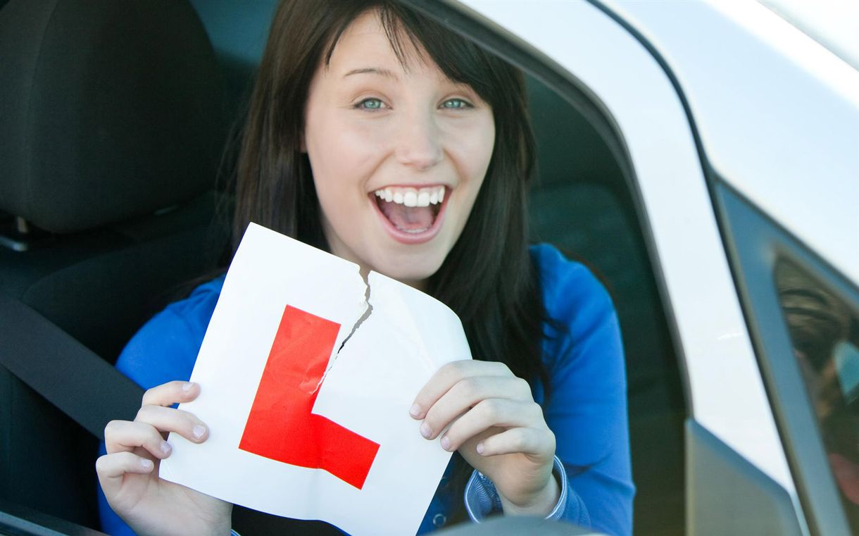 A woman ripping up a L-plate after passing her driving test